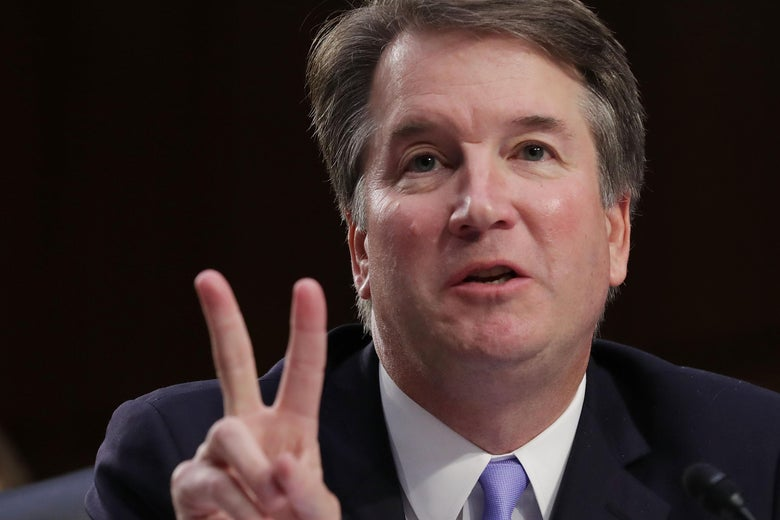 Brett Kavanaugh, making what looks like a peace sign but is probably just meant to indicate the number two.