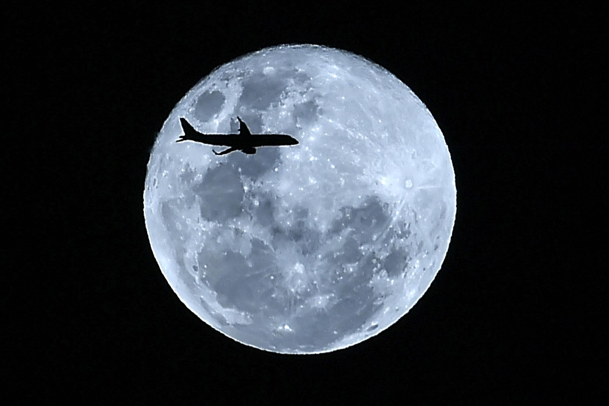 A plane in flight is silhouetted against the 'super blue moon' over Cali, Colombia on January 31, 2018.