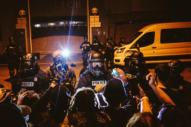 Protesters, some holding up phones, facing police in riot gear