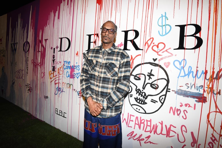 Snoop Dogg stands in front of a heavily graffiti'd white wall.