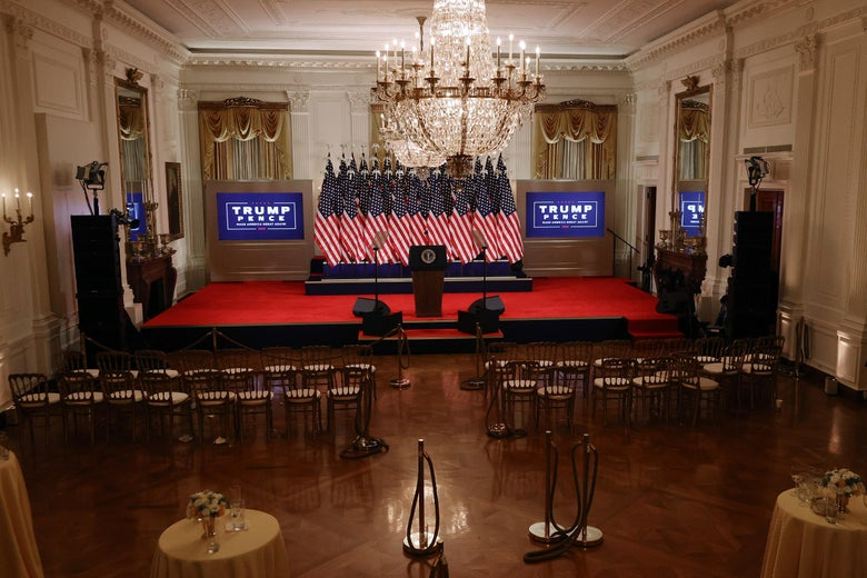 A room empty of people, with rows  of vacant chairs facing a presidential lectern on a red-carped stage, backed by a solid mass of American flags on flagpoles and flanked by Trump-Pence logos on screens.