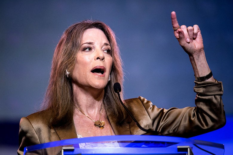 Marianne Williamson gestures while speaking from a podium.