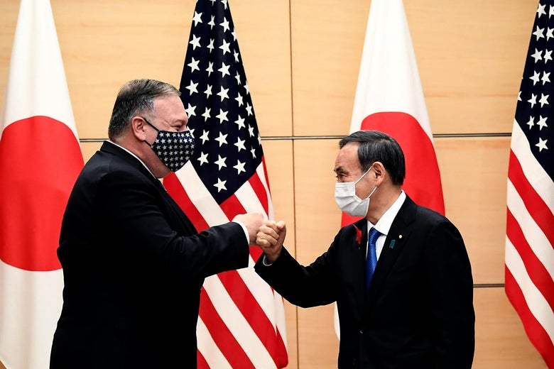 Japan's Prime Minister Yoshihide Suga and then-Secretary of State Mike Pompeo (L) bump fists as they meet at the prime minister's office in Tokyo on October 6, 2020.