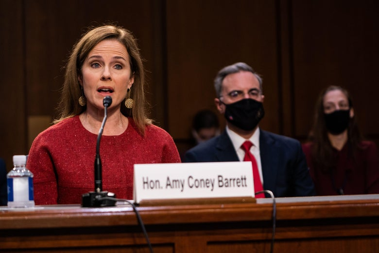 """A woman in a red sweater speaking into a microphone sits behind a nameplate that says, """"Hon. Amy Coney Barrett."""""""