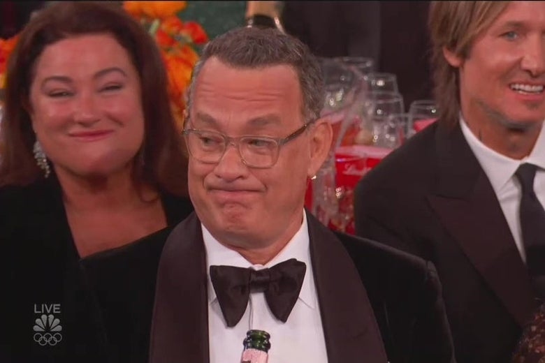 Tom Hanks, sitting at a table at the Golden Globes, making an unimpressed face.