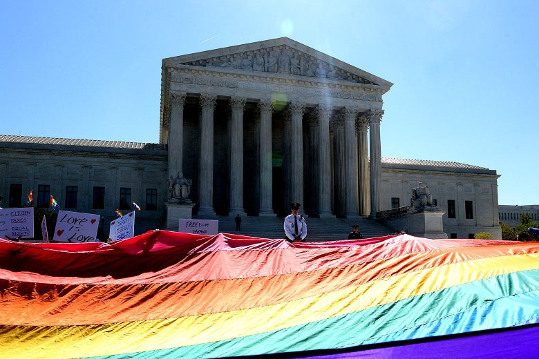 Protesters hold pro–gay rights flags outside the U.S. Supreme Court on April 28, 2015, in Washington, D.C.