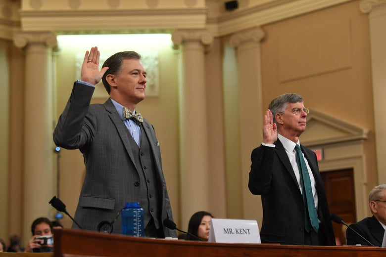 Kent and Taylor in the hearing room, raising their right hands to be sworn in.
