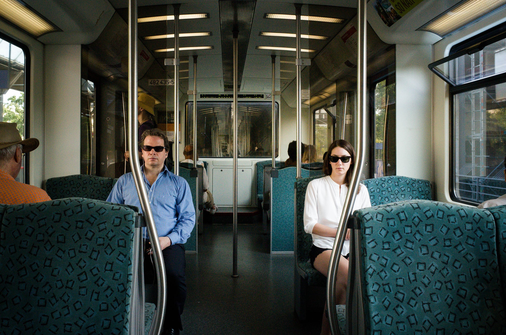 Picture of a man and a woman wearing sunglasses on public transportation.