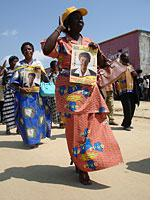 A woman holds a poster for a legislative candidate from the PPRD, the party of President Joseph Kabila.Click image to expand.