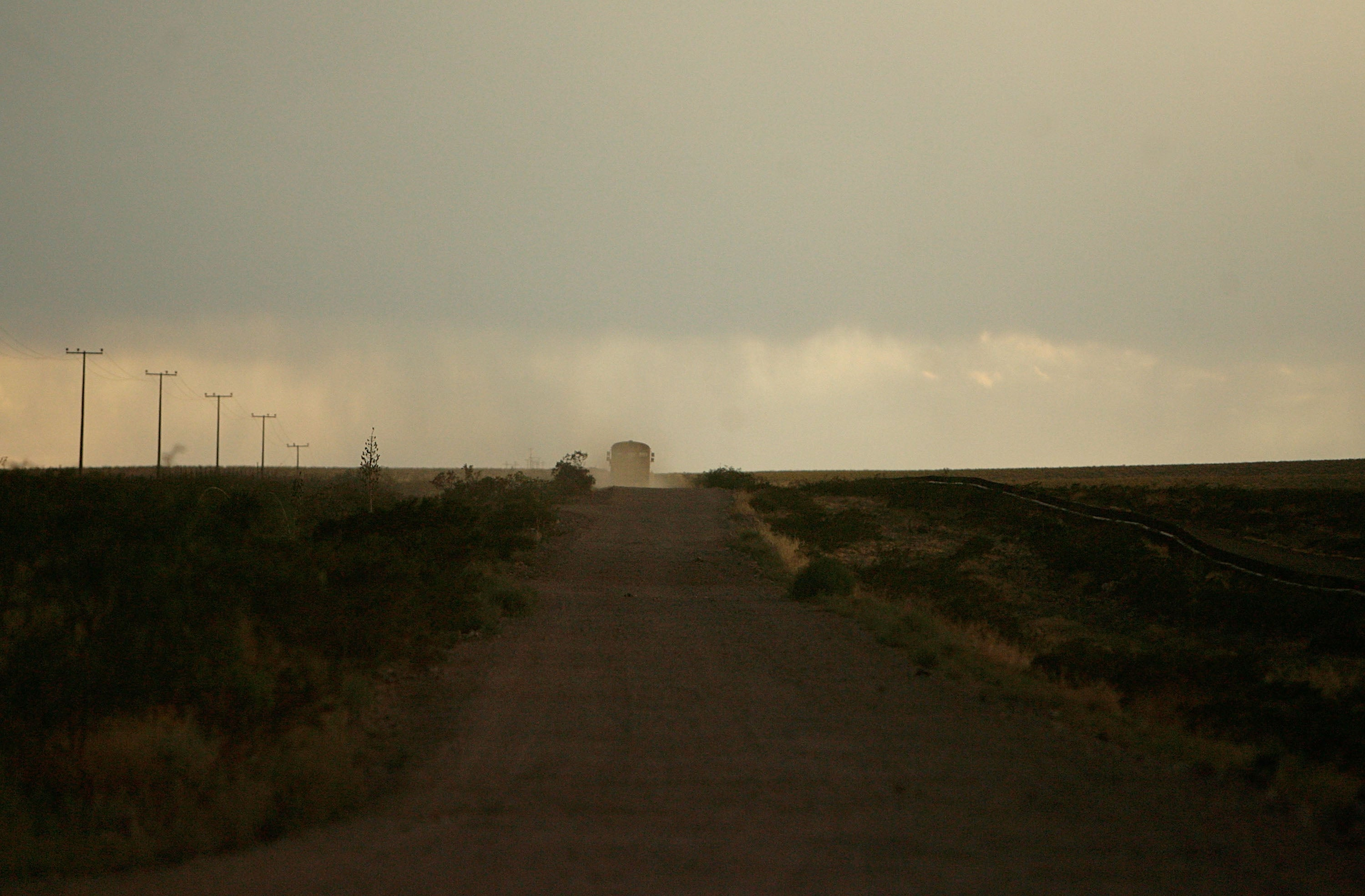 A bus is seen in the distance on a dirt road through the dust and sparse brush of a desert at dusk.