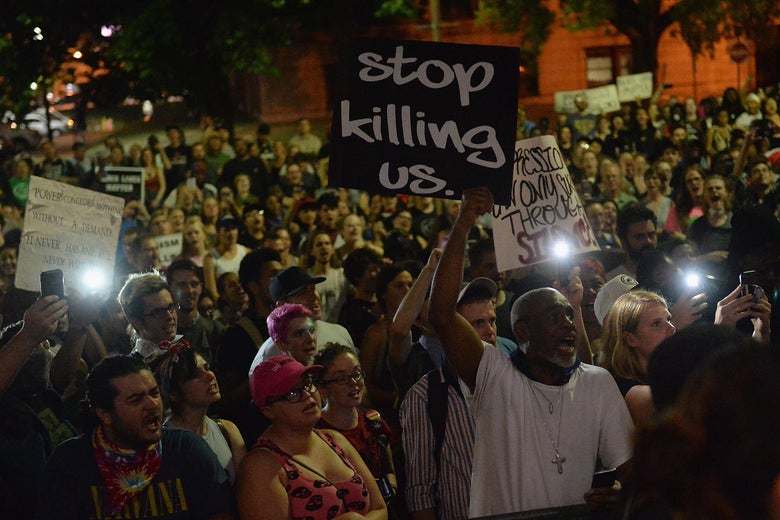 """A few people hold lights from their cell phones at a night-time protest. A man in a white tee shirt at the front holds a sign that says, """"stop killing us."""""""