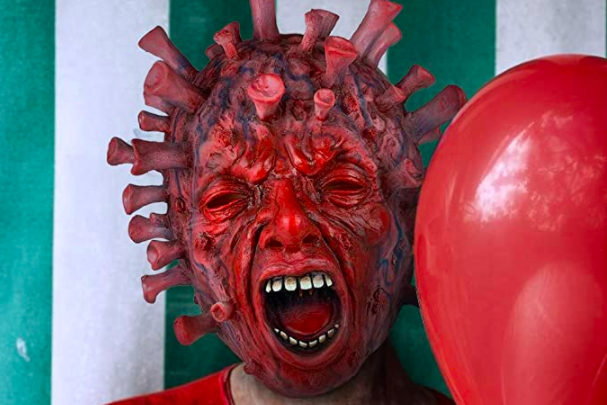 Someone wearing a latex scary coronavirus mask, next to a red balloon and against a green-and-white striped background.