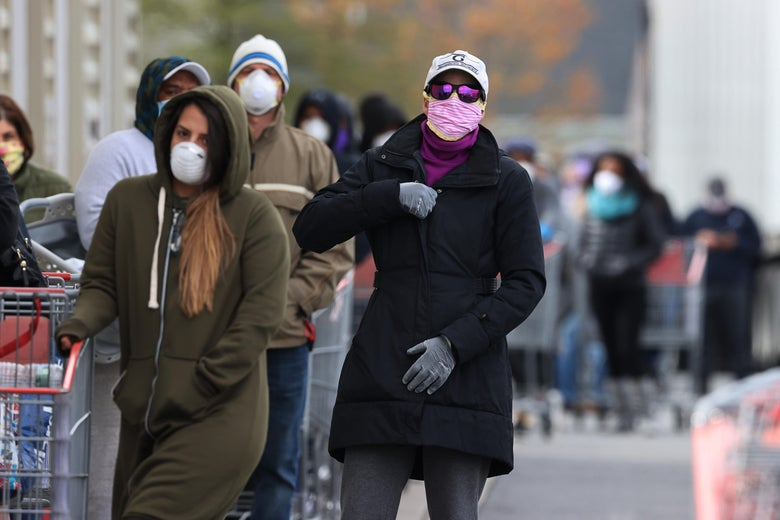 A long line of customers wearing masks and winter coats and pushing shopping carts