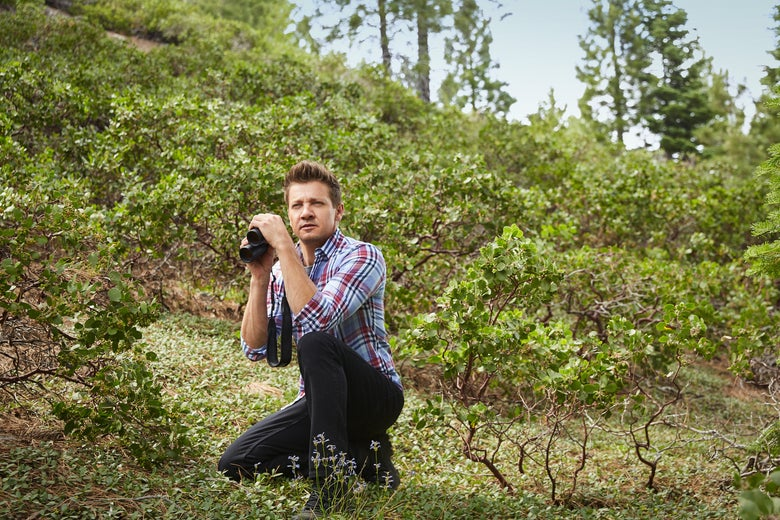 Jeremy Renner crouches in the wilderness, holding a pair of binoculars but not looking through them.