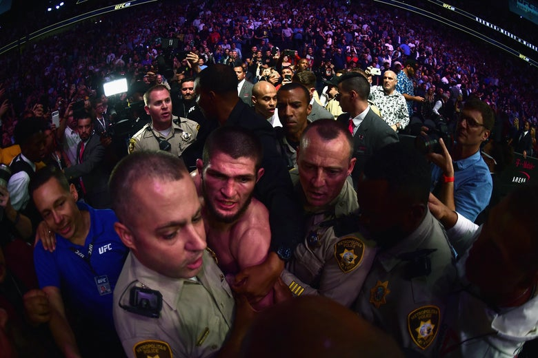 LAS VEGAS, NV - OCTOBER 06:  Khabib Nurmagomedov of Russia is escorted out of the arena after defeating Conor McGregor of Ireland in their UFC lightweight championship bout during the UFC 229 event inside T-Mobile Arena on October 6, 2018 in Las Vegas, Nevada.  (Photo by Harry How/Getty Images)