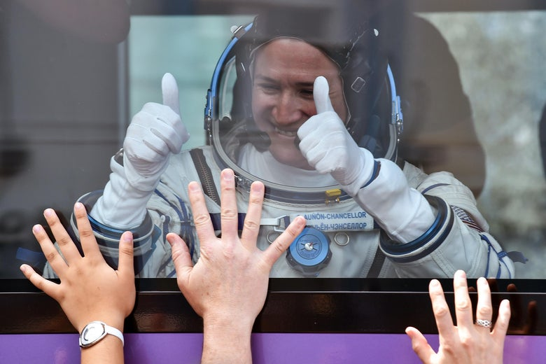 Female astronaut in spacesuit giving the thumbs-up to waving onlookers.
