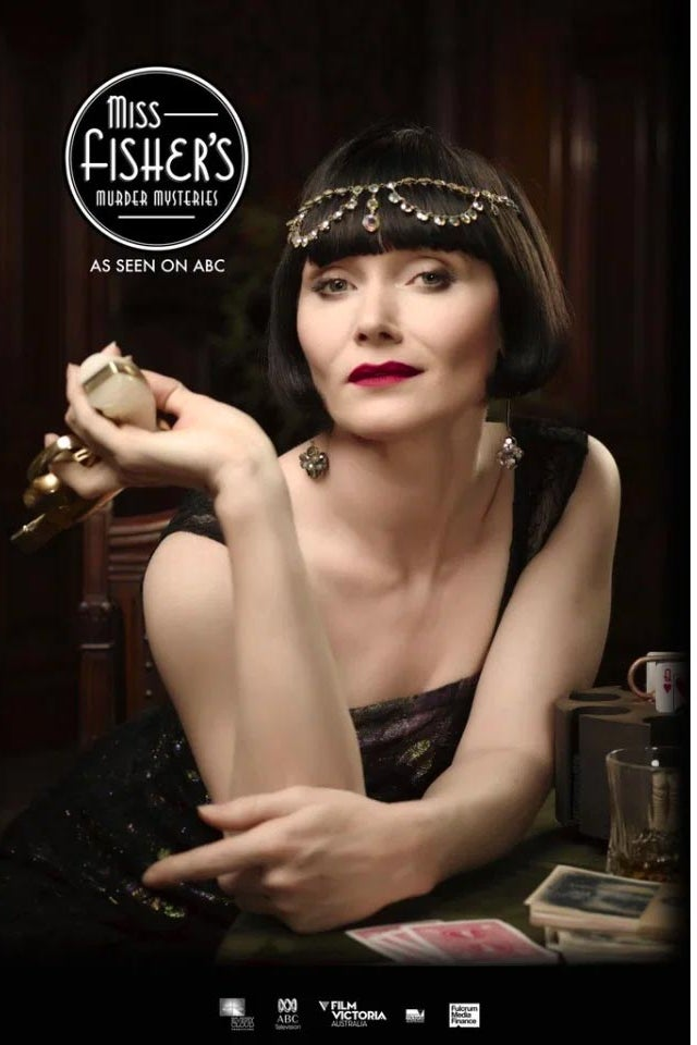Essie Davis, her hair in a blunt black bob, leans on a table with playing cards on it.