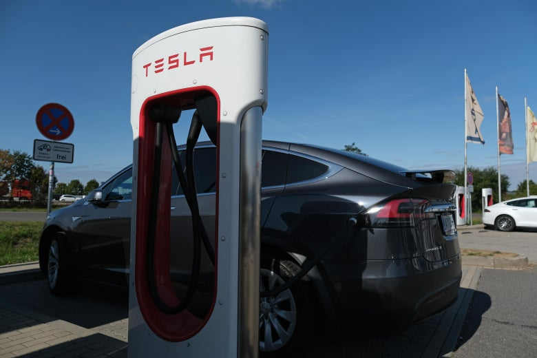A Tesla electric car charges at a highway rest stop.