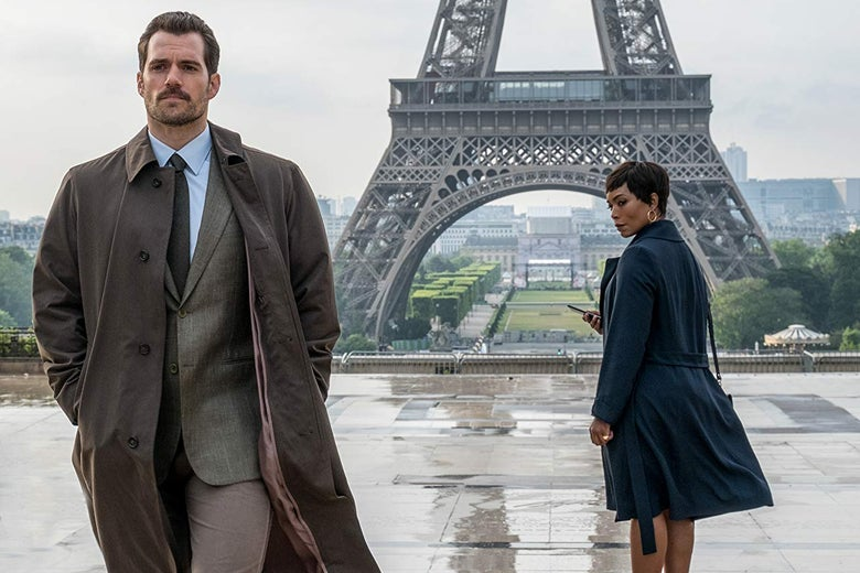 Angela Bassett stares after Henry Cavill, who walks toward the camera. The bottom of the Eiffel Tower is in the background.