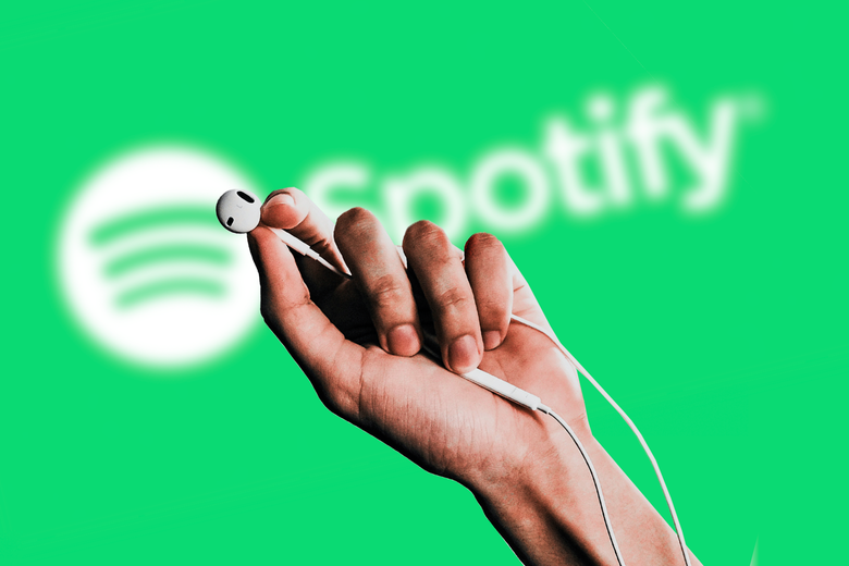 Hand holding wired Apple earphones in front of the Spotify logo