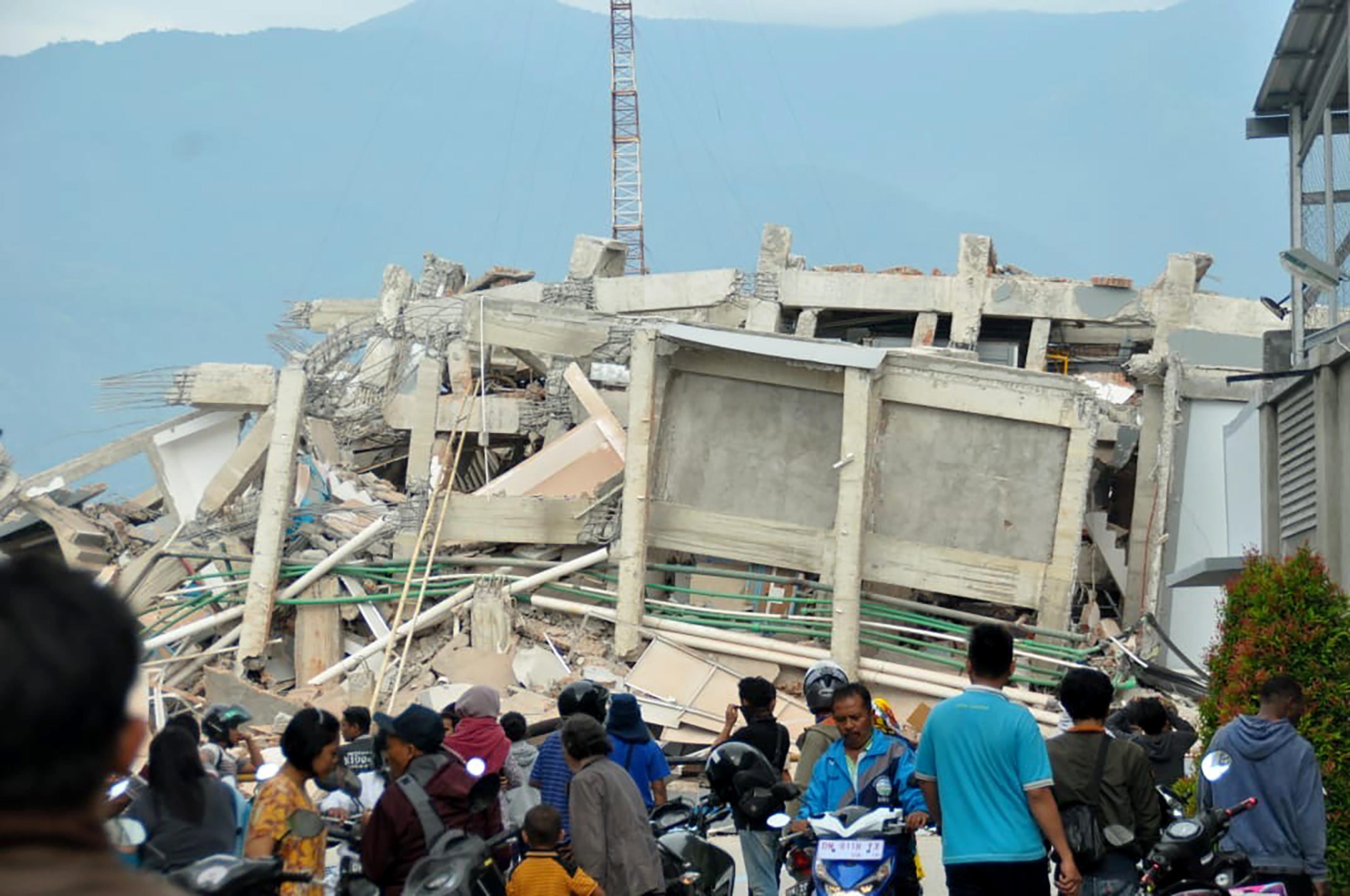 Residents gather to look at a collapsed building after an earthquake and tsunami hit Palu.