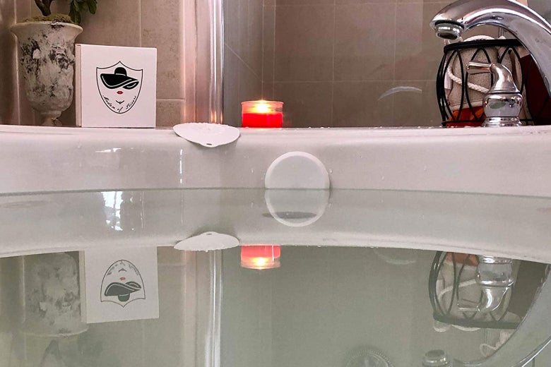 Bathtub full of water with overflow drain covered and a lit candle on the ledge