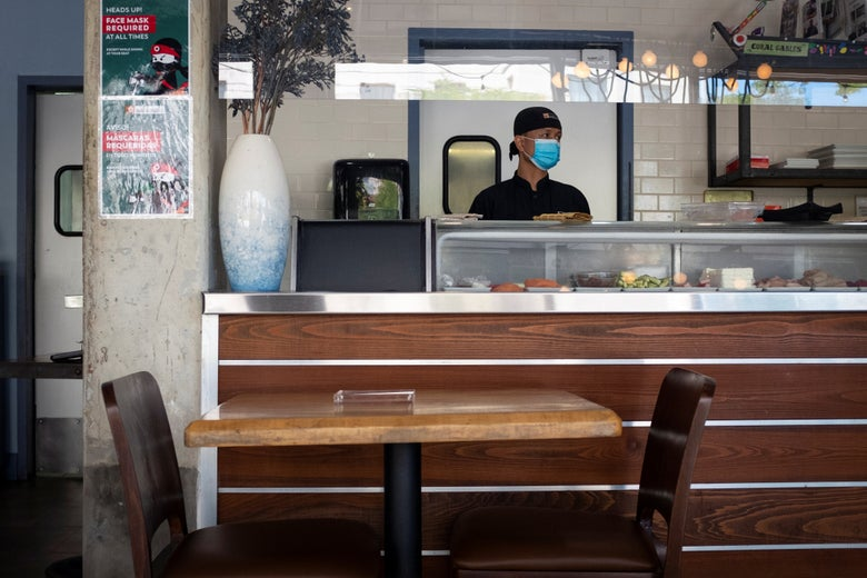 Sushi chef wearing mask in empty restaurant