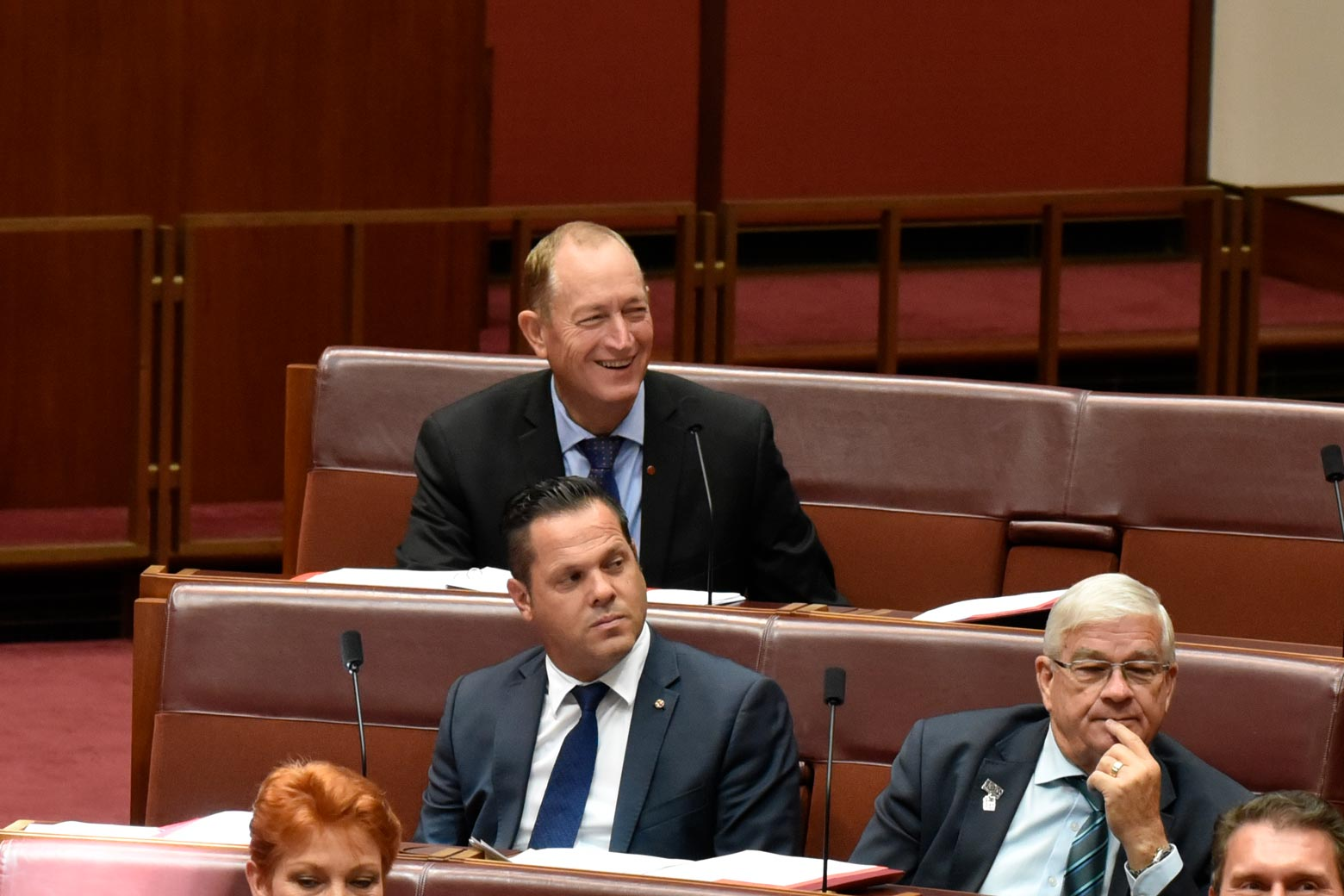 Fraser Anning and other senators sit in chairs in Parliament.