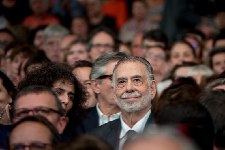 Francis Ford Coppola smiling serenely in a crowd in Lyon, France.