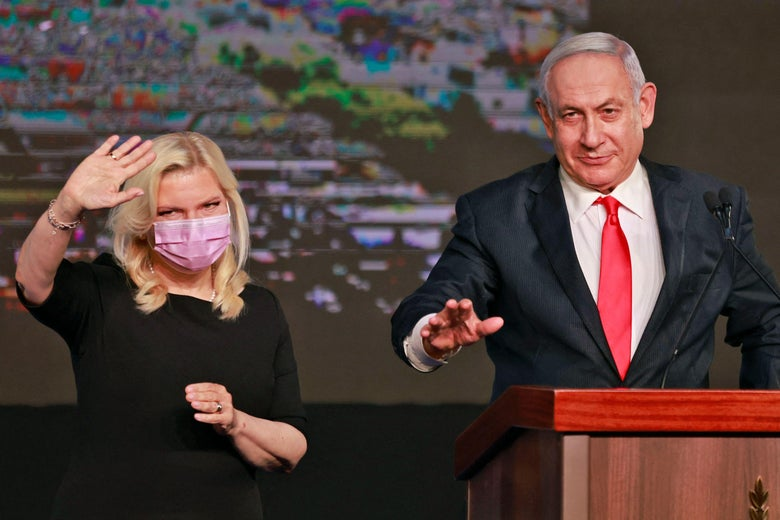 Sara waves to the crowd as she stands next to Benjamin Netanyahu, who is at a podium