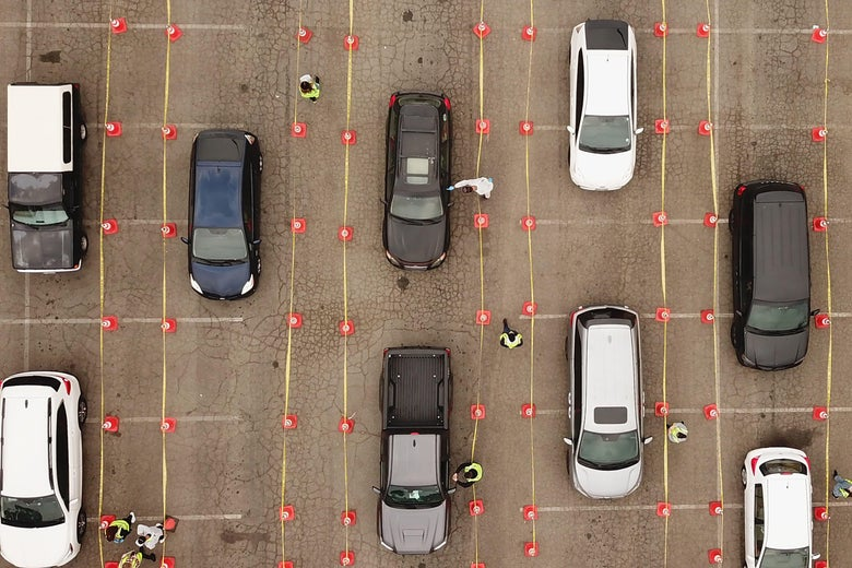 An aerial view of 9 cars waiting in line at a COVID-19 testing site.