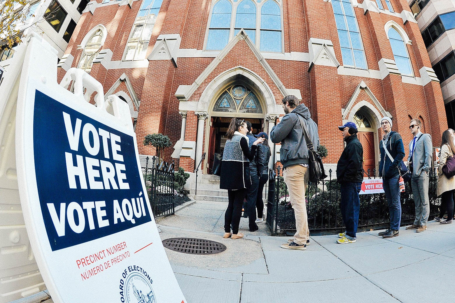 """A """"Vote Here/Vote Aqui"""" sign is seen outside the front of a church where people stand in line to go in."""