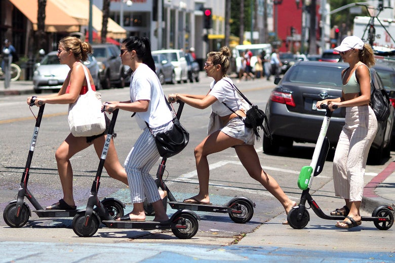 Four women ride e-scooters to cross a city street