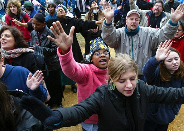 Worshipers raise their hands as they pray during the America for Jesus rally on Oct. 22, 2004, in Washington, D.C.