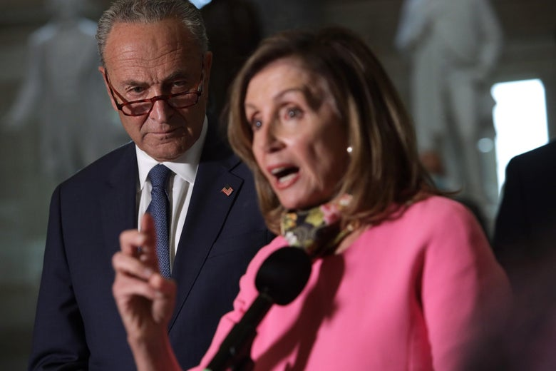 Schumer, glancing above his glasses, looks over Pelosi's shoulder as she speaks into a microphone.