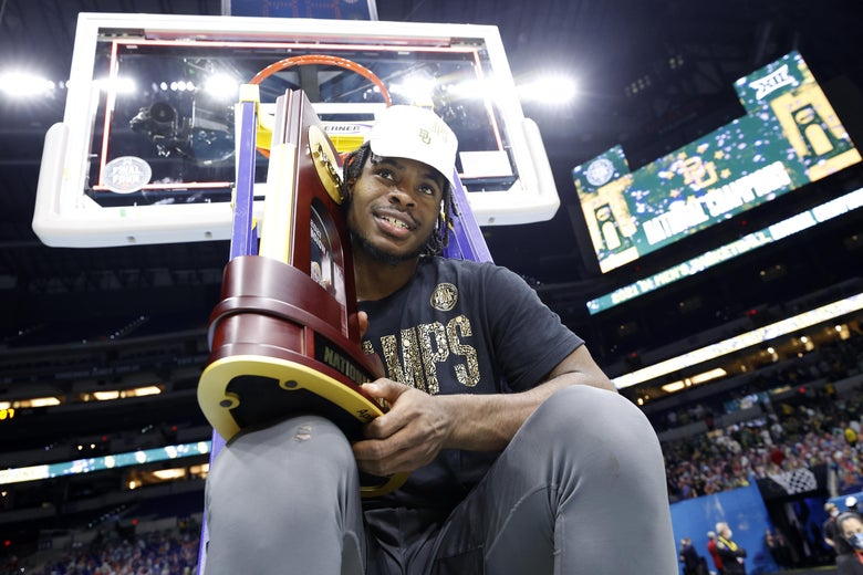 Baylor's Davion Mitchell smiling, sitting on a ladder under the hoop, with the NCAA title trophy