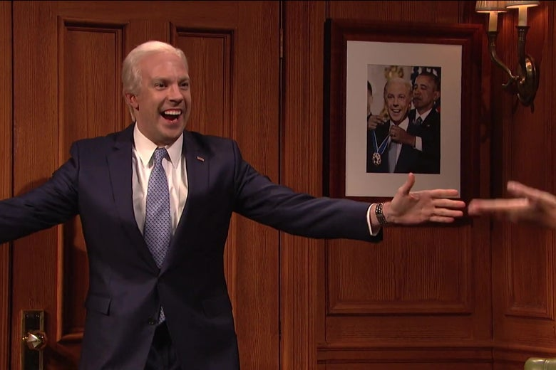 Jason Sudeikis, as Joe Biden, stands in front of a Photoshopped photo of Obama putting a medal around Sudeikis' neck as Sudeikis grins like a moron.