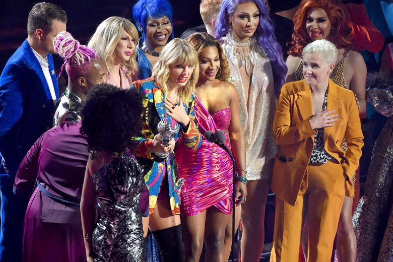 "Taylor Swift holds an award onstage, surrounded by people from the ""You Need to Calm Down"" video."
