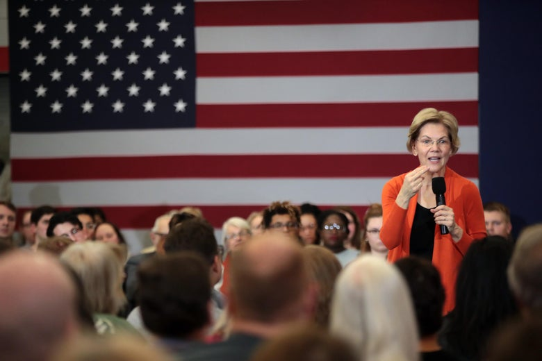 Elizabeth Warren speaks to a crowd, with an American flag in the background.