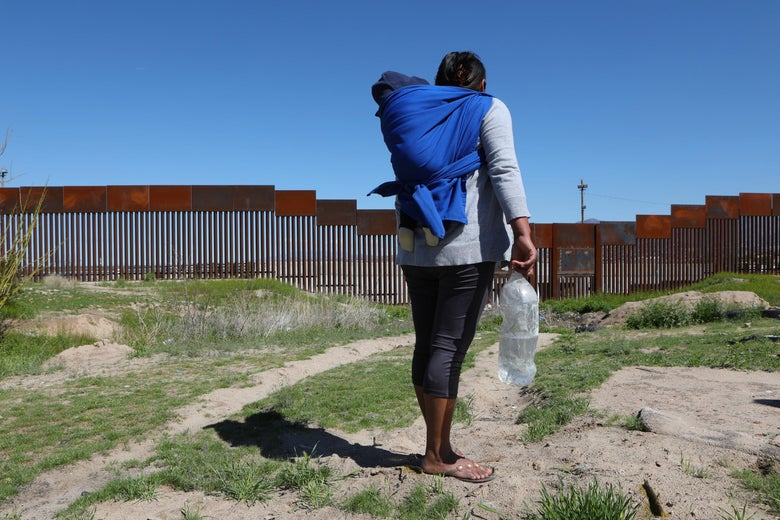 A migrant carrying a toddler stands in front of the border wall that divides New Mexico, United States, with Ciudad Juarez, state of Chihuahua, Mexico.