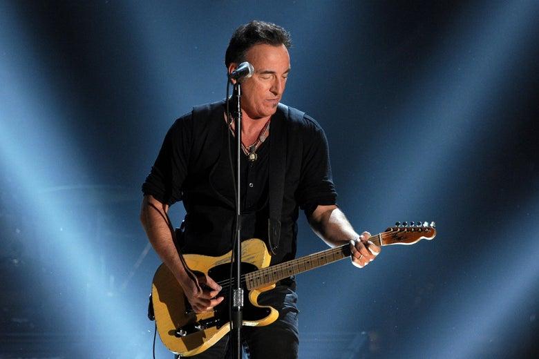 Springsteen plays guitar onstage.