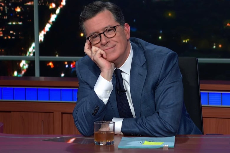 Stephen Colbert sits at his Late Show desk, a glass of Scotch and a script in front of him.