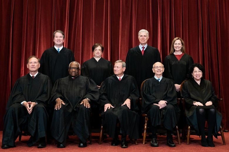 Associate Justice Samuel Alito, Associate Justice Clarence Thomas, Chief Justice John Roberts, Associate Justice Stephen Breyer, and Associate Justice Sonia Sotomayor seated with Associate Justice Brett Kavanaugh, Associate Justice Elena Kagan, Associate Justice Neil Gorsuch, and Associate Justice Amy Coney Barrett standing behind them. All are wearing their robes for a group photo in front of a red curtain.