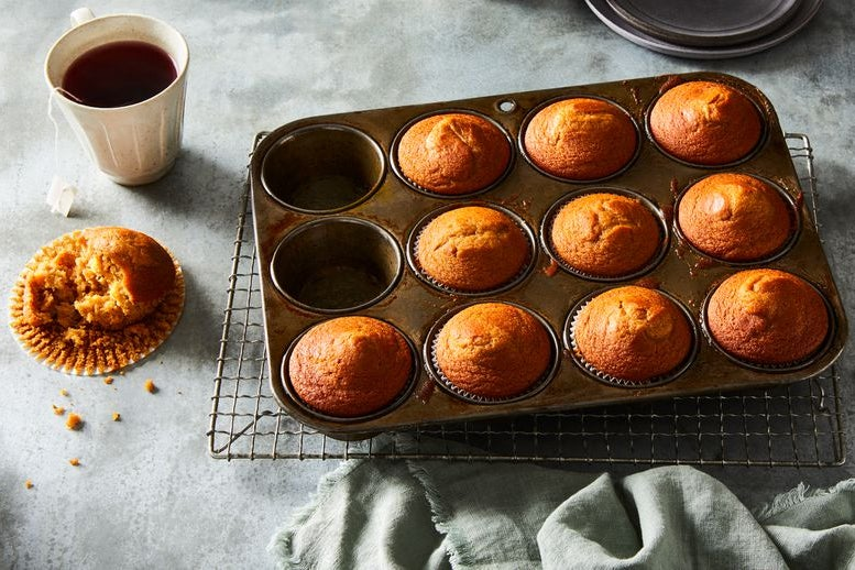 Muffins in a baking pan sit next to a cup of tea and a half-eaten muffin in its wrapper, crumbs spilling onto the countertop