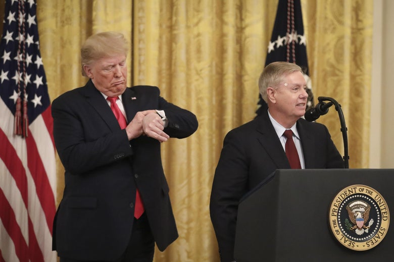 Donald Trump checks his watch  as he stands behind Lindsey Graham, who is at a lectern.