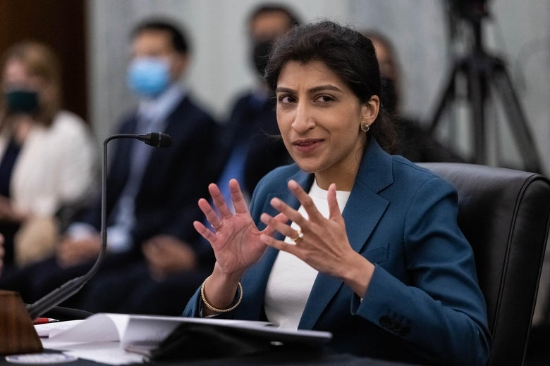 Lina Khan gesticulates while speaking into a mic.