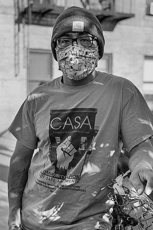 Andrés Vargas stands in front of a building wearing a beanie, a face mask, and a T-shirt reading CASA.