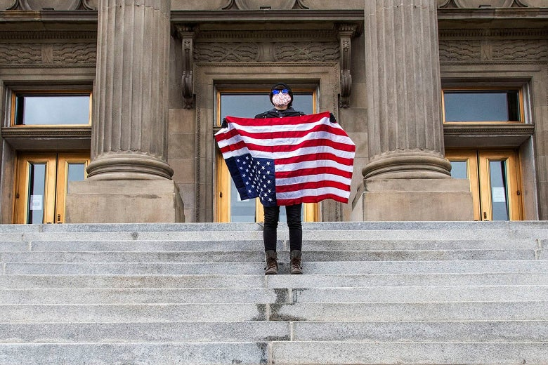 A student holding a U.S. flag upside down stands atop the steps at the Idaho Capitol Building on April 26 in Boise, Idaho.