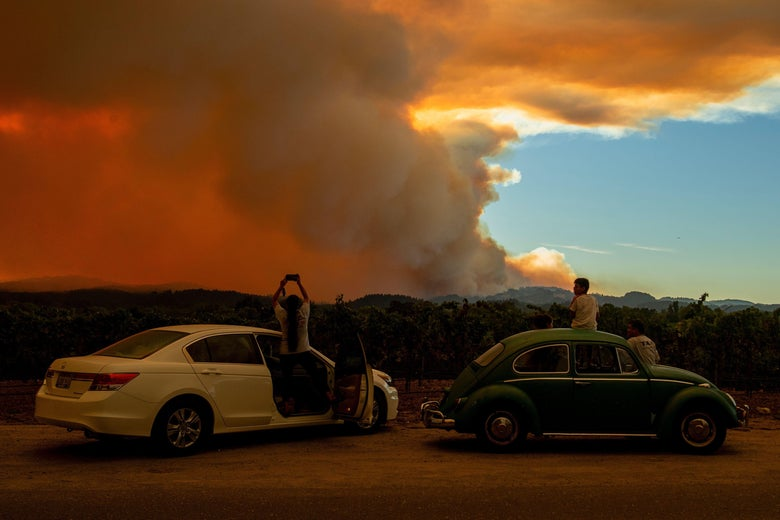 People stand outside of two cars to watch as smoke takes over the sky.