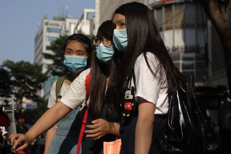 Three women wearing protective masks